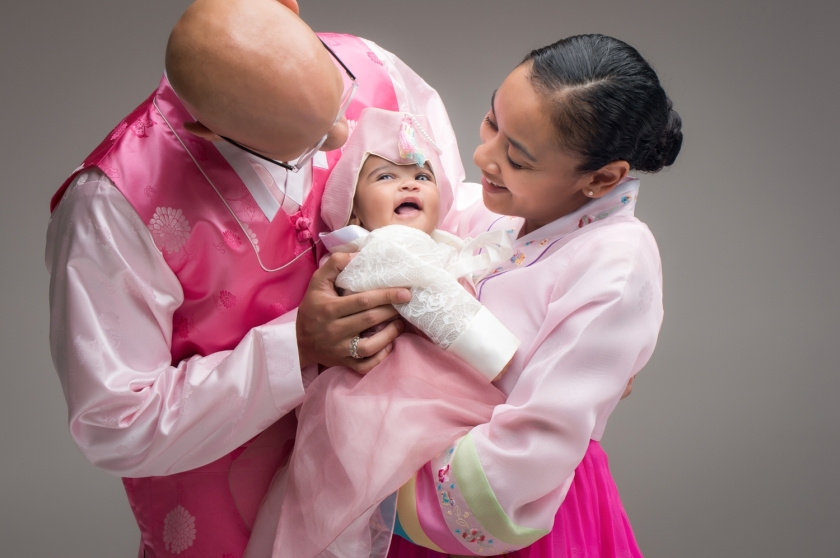 Parents play with baby in traditional Korean dress during 100-day-old photoshoot.