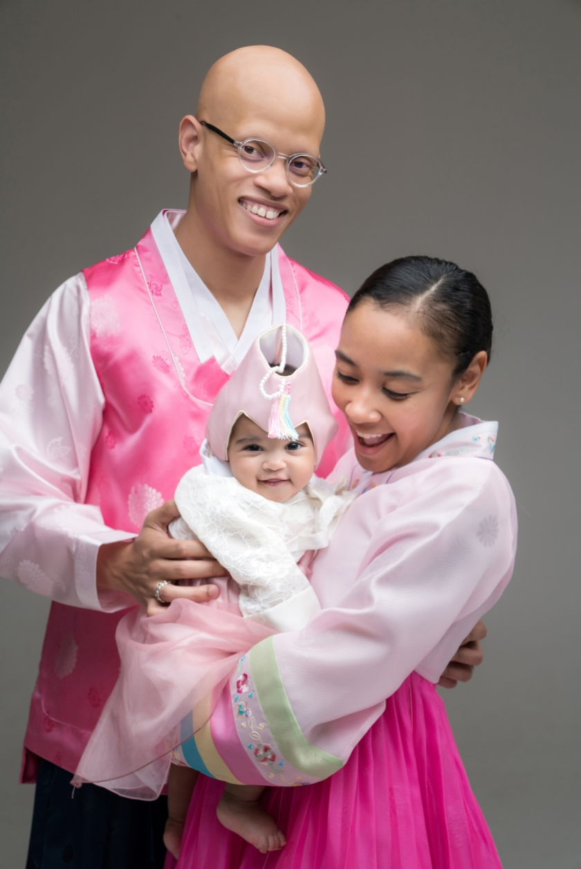 Family poses for portraits in Chicago photo studio for 100-day-old Korean photoshoot.