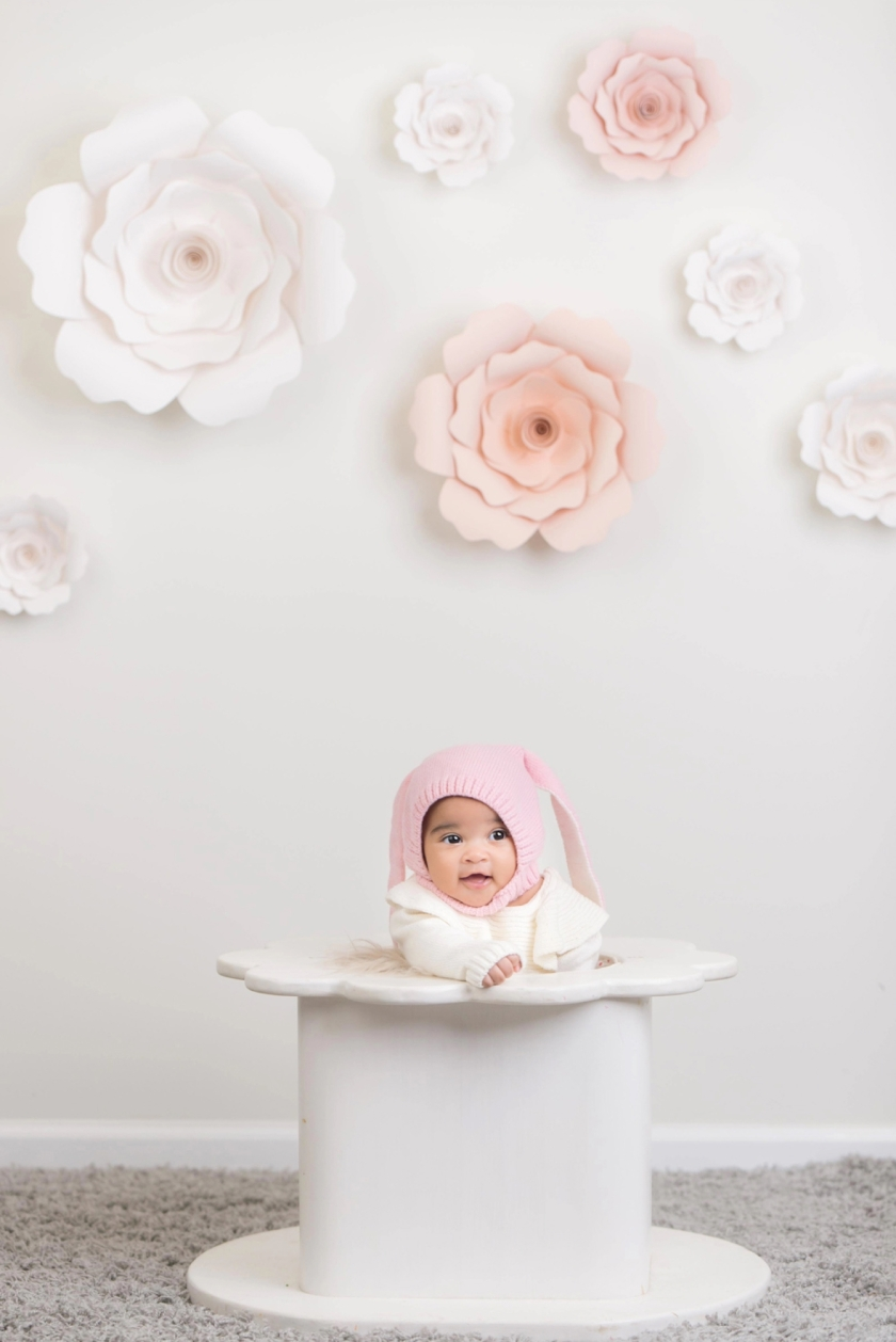 100-day-old baby girl poses for portraits in a pink hat.
