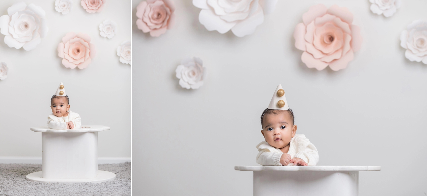Baby girl wears a pointed party hat with gold decorations during baby photo session.