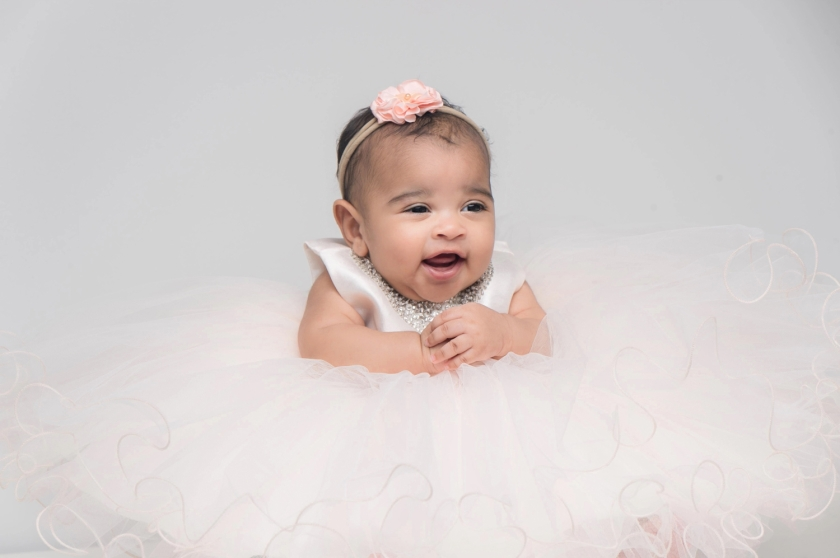 Baby girl wears a large pink tutu during a photoshoot.
