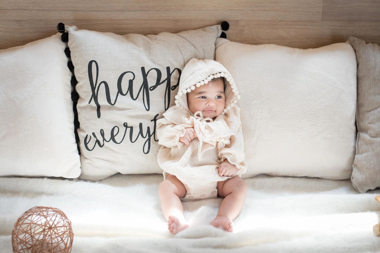 Month-old baby smiles during a newborn photo session.