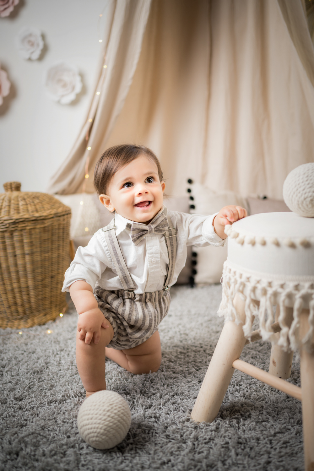 Baby kneels on shag carpet during baby photoshoot.