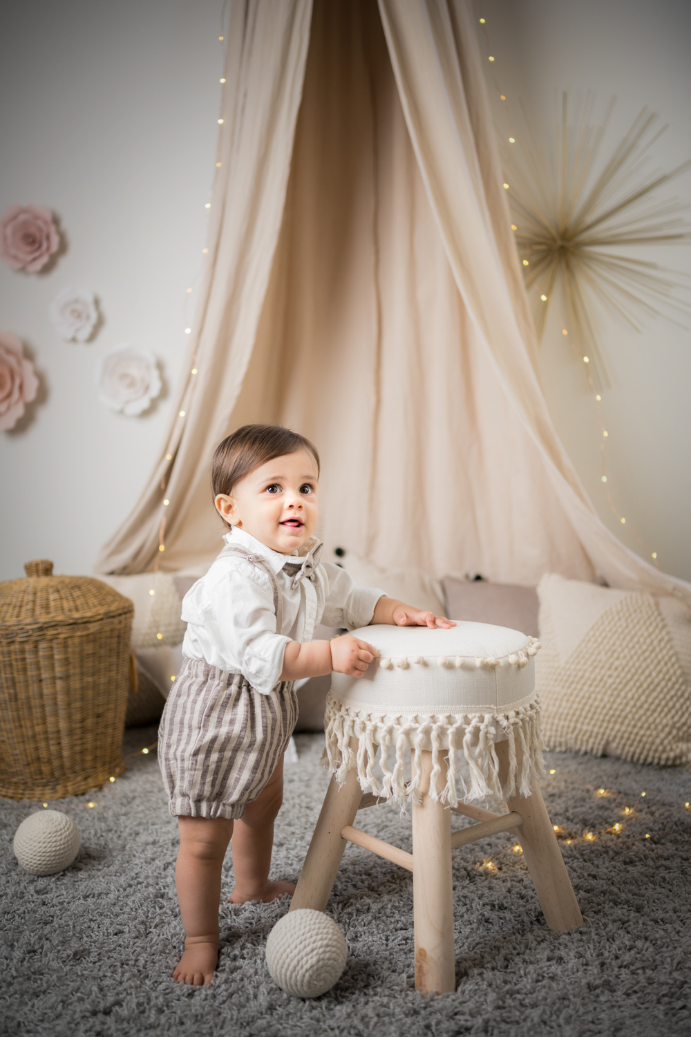 Baby boy holds onto a decorative stool during a photo session.
