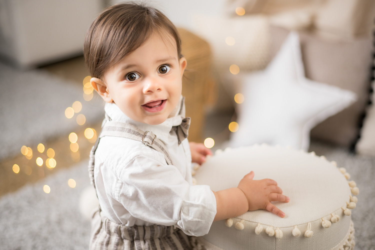 Baby stands in front of string lights and star pillows and smiles.
