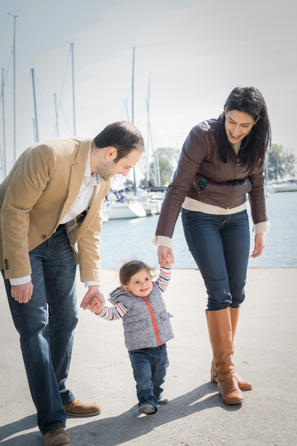 Parents hold son's hands as he walks on the shore of Lake Michigan.