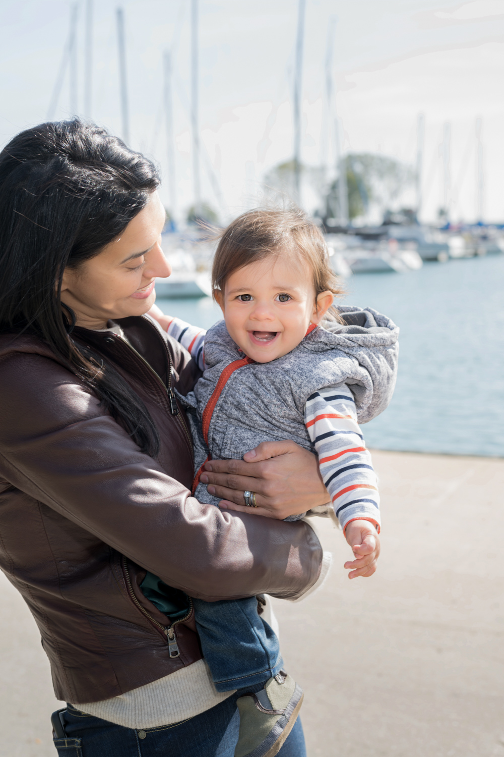 Mom holds son by docks on Lake Michigan.