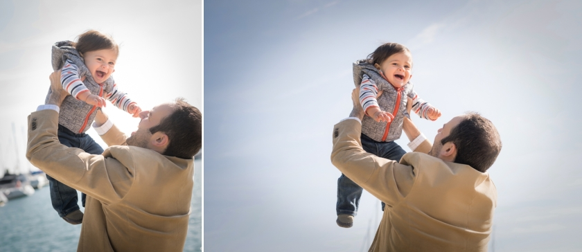 Dad holds smiling son over his head by Lake Michigan.