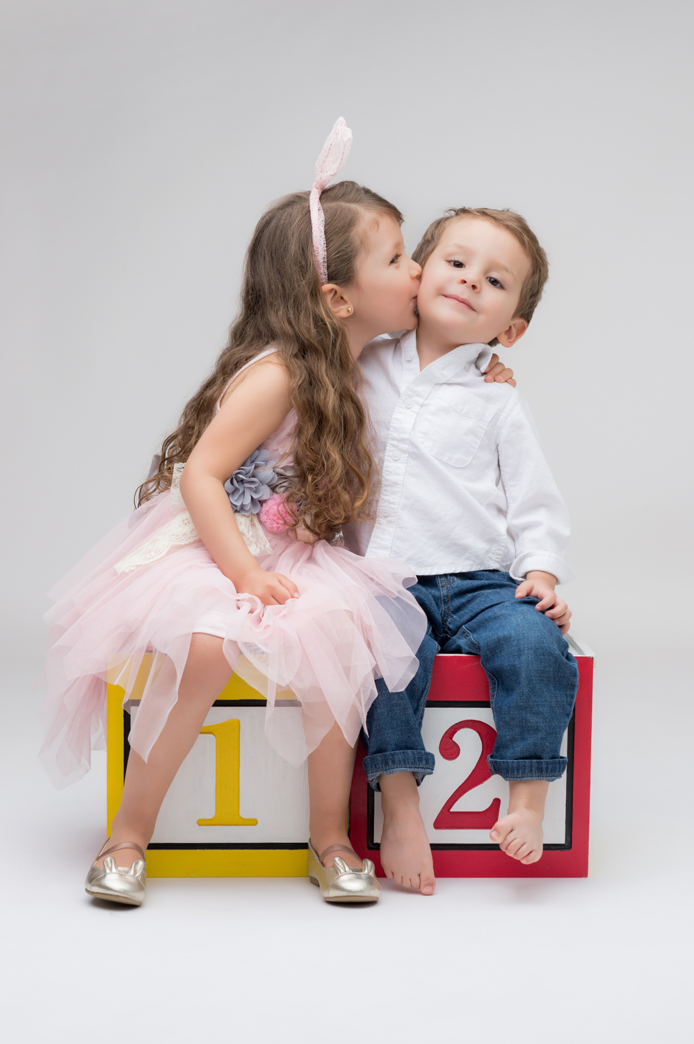Older sister kisses her little brother on the cheek.