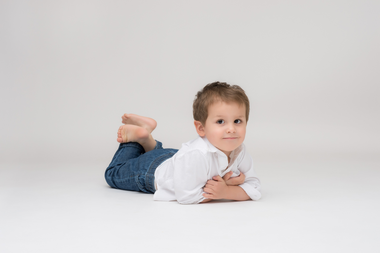 Little boy poses in Chicago photo studio for portraits.