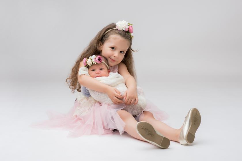 Older sister hugs her newborn baby sister.