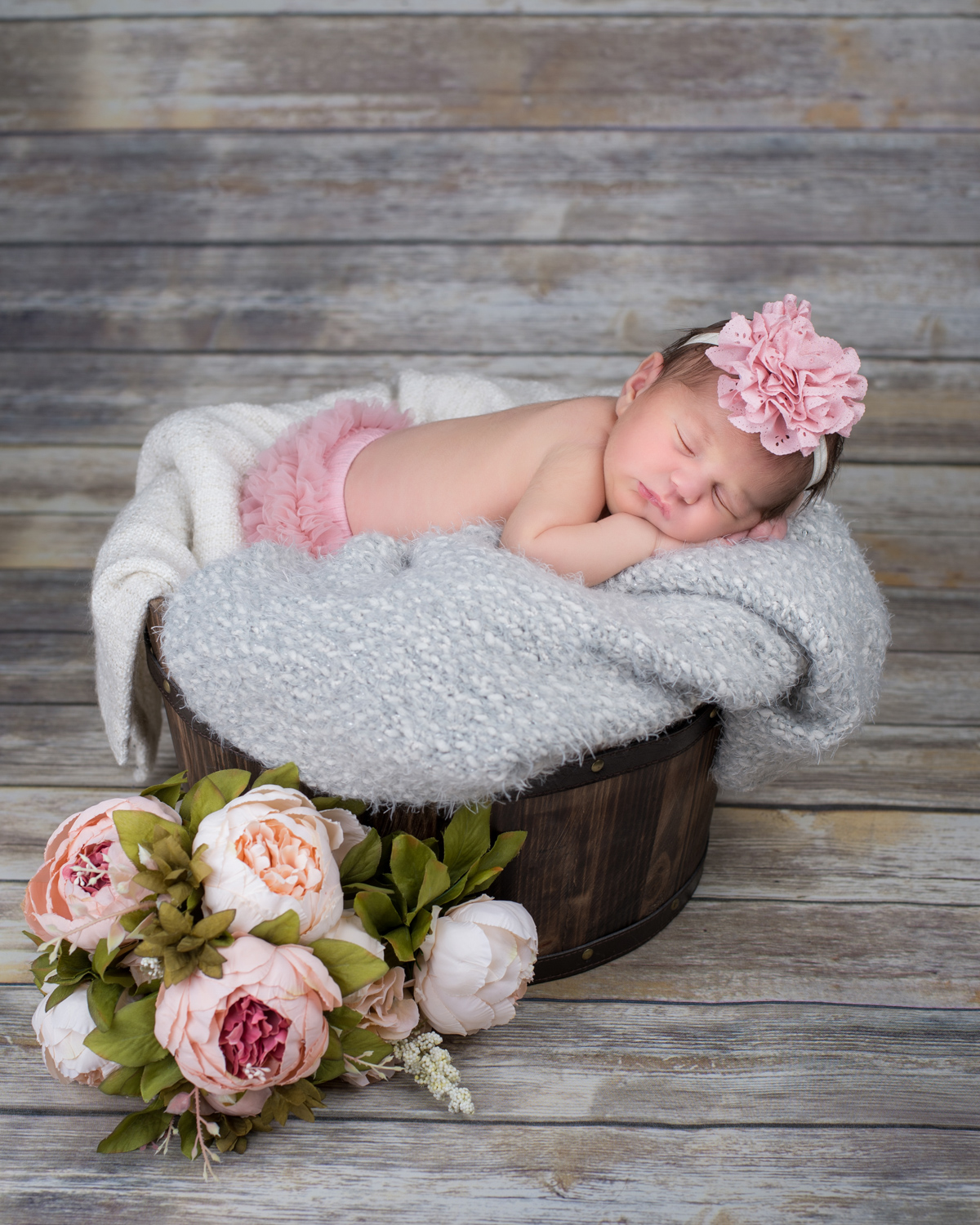 Newborn baby sleeps on a grey blanket in a bucket with pink flowers.