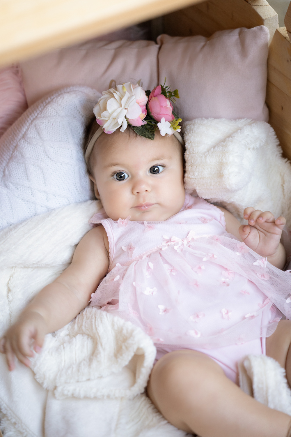 A newborn baby wearing a pink dress lies in a crib with a white blanket.