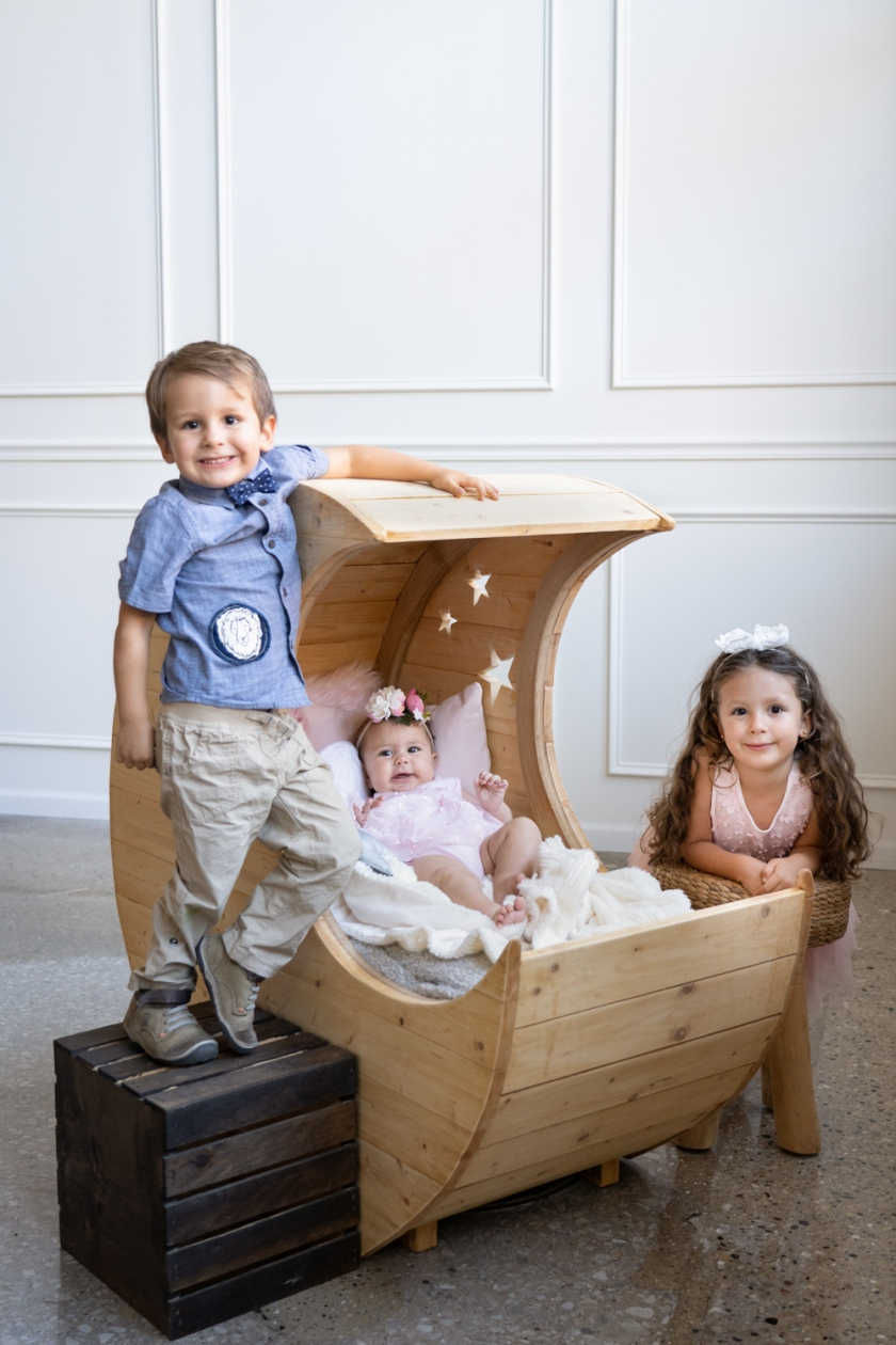 A little boy and little girl pose around their baby sister's moon shaped crib.