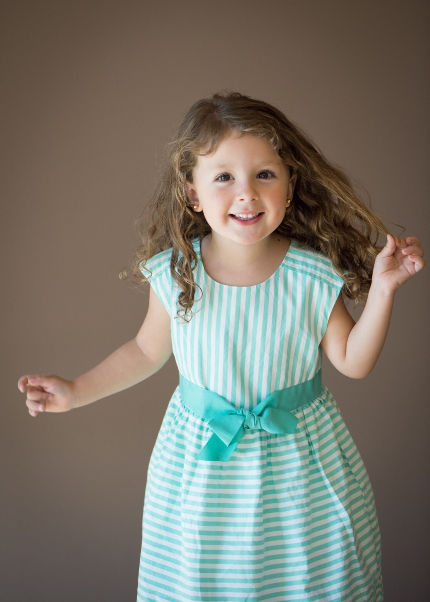 Little girl in green-stripped dress dances during Easter photo session.