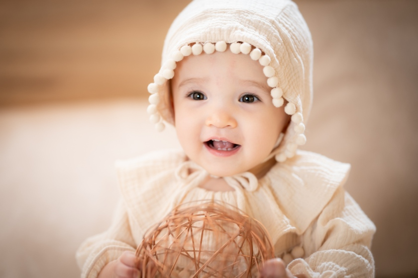 Baby holds ball and smiles during baby photoshoot.