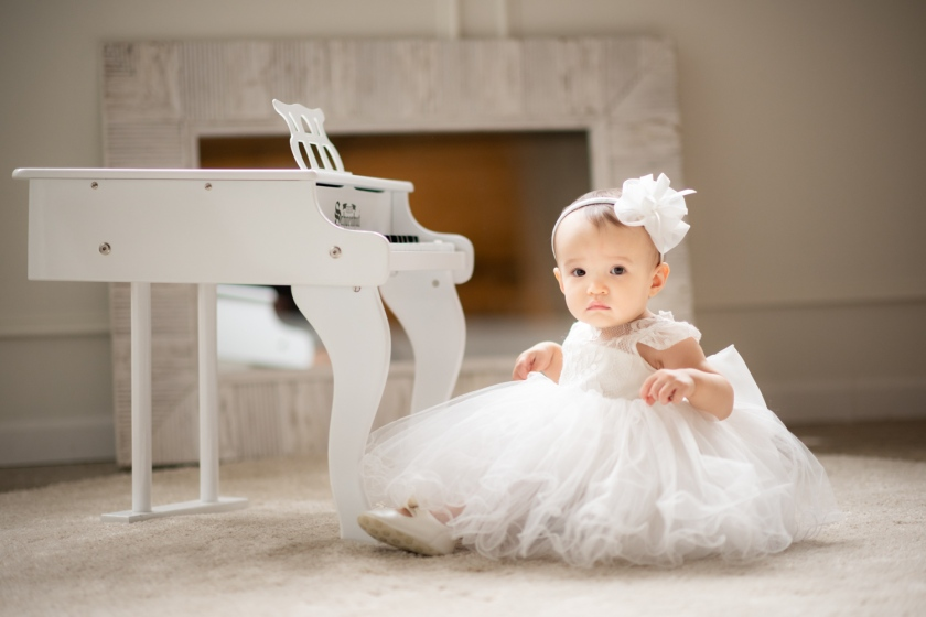 Baby in poufy white dress sits in front of miniature white piano.