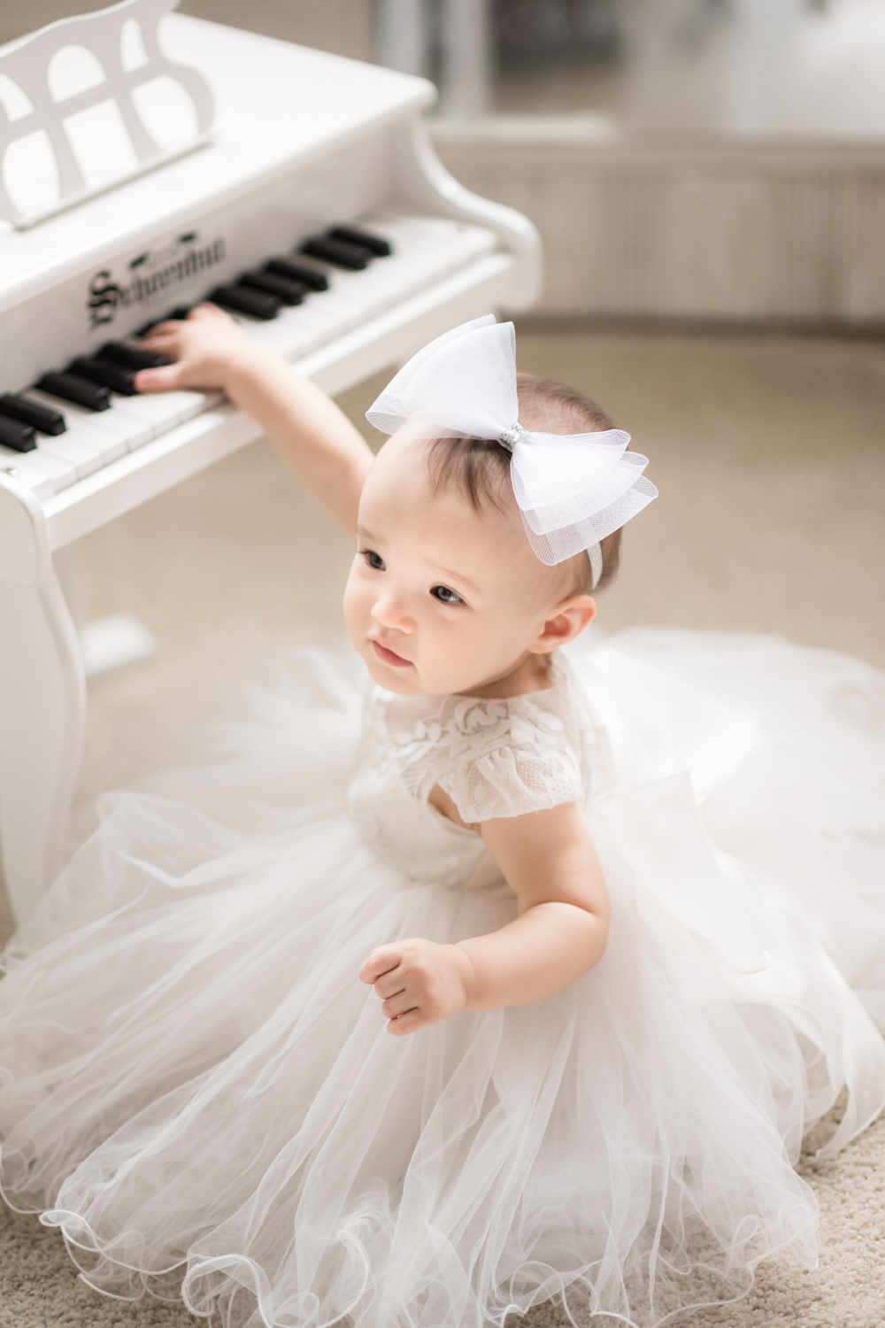 Baby girl plays miniature piano during birthday photo session in Chicago.