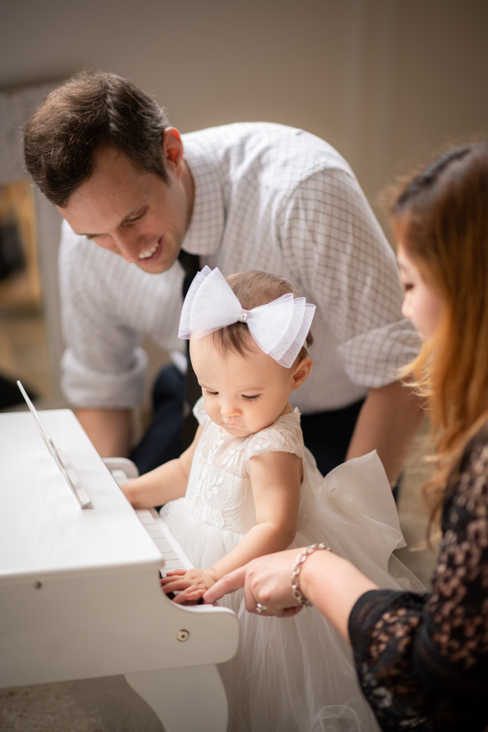 Parents play the piano with their one-year-old daughter in Chicago photo studio.