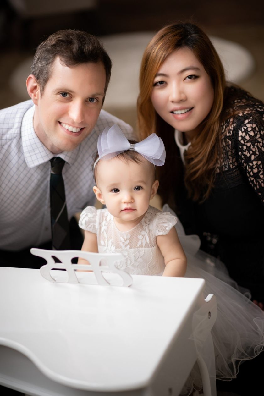 Parents smile with baby during family photo session.