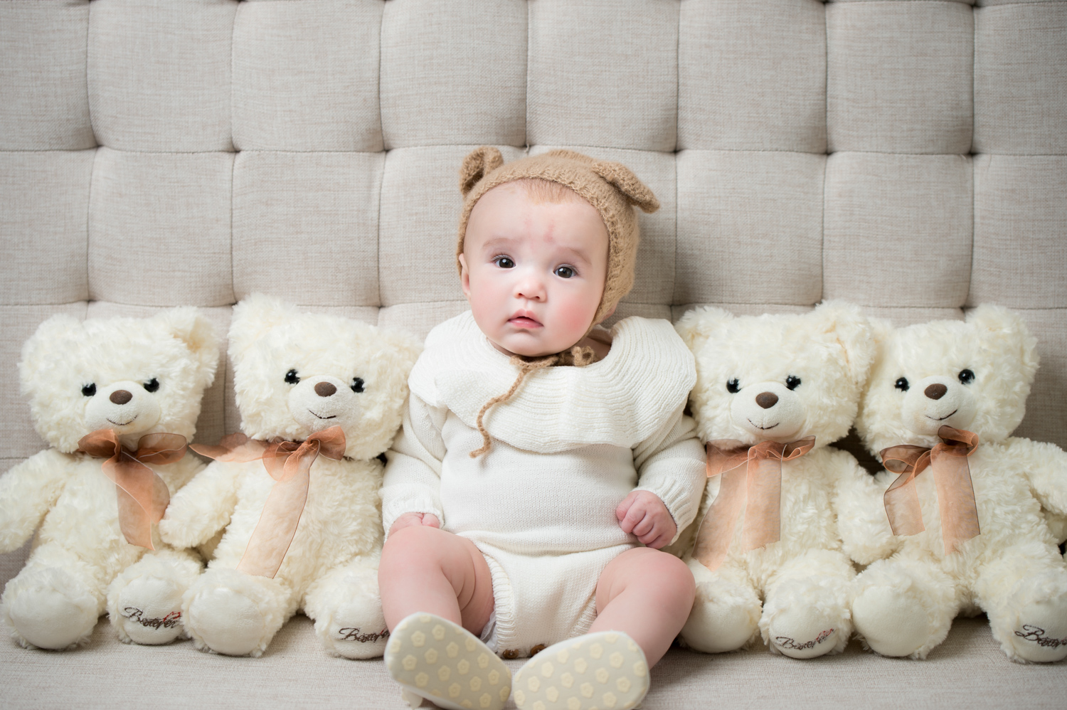 Layla sits in the middle of white teddy bears for her 100th day photo shoot.