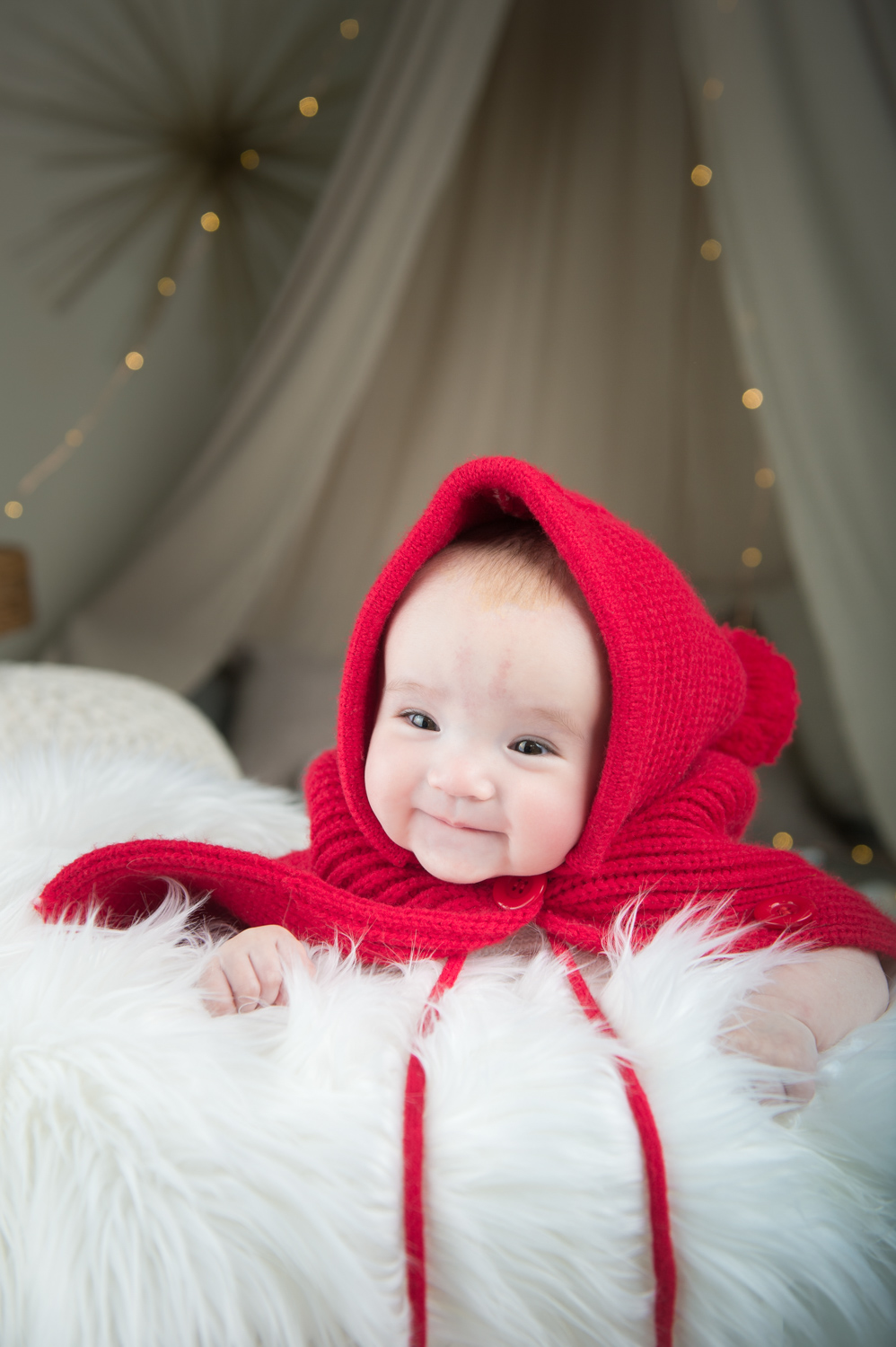 Baby wears red cape on white fur blanket during traditional Korean 100th day photoshoot.