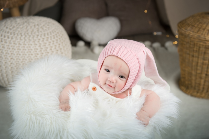Layla wears white dress and pink hat during baby photoshoot.