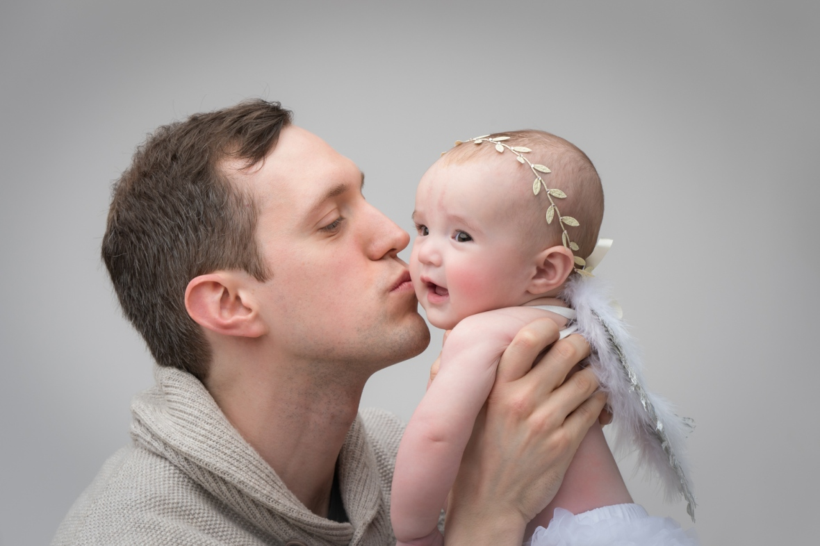 Dad kisses 100-day-old baby during photoshoot.