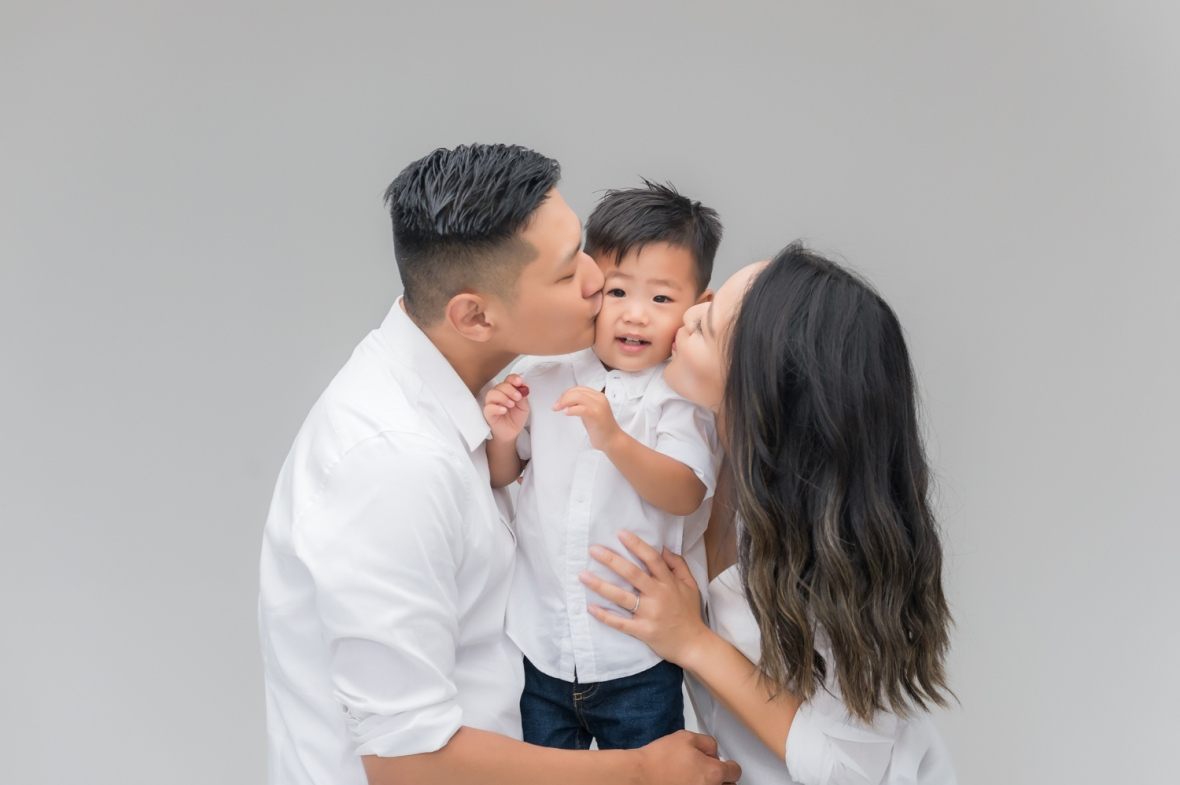 Henry's parents kiss his face during family photoshoot in Chicago photo studio.