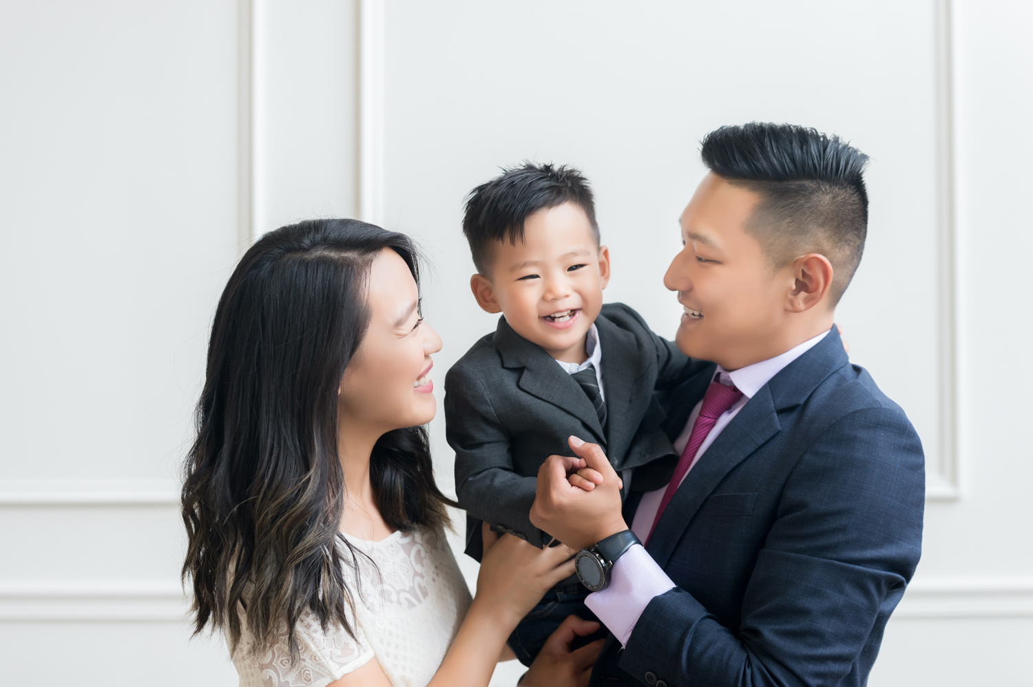 Parents smile at son during a family photo session in Chicago.