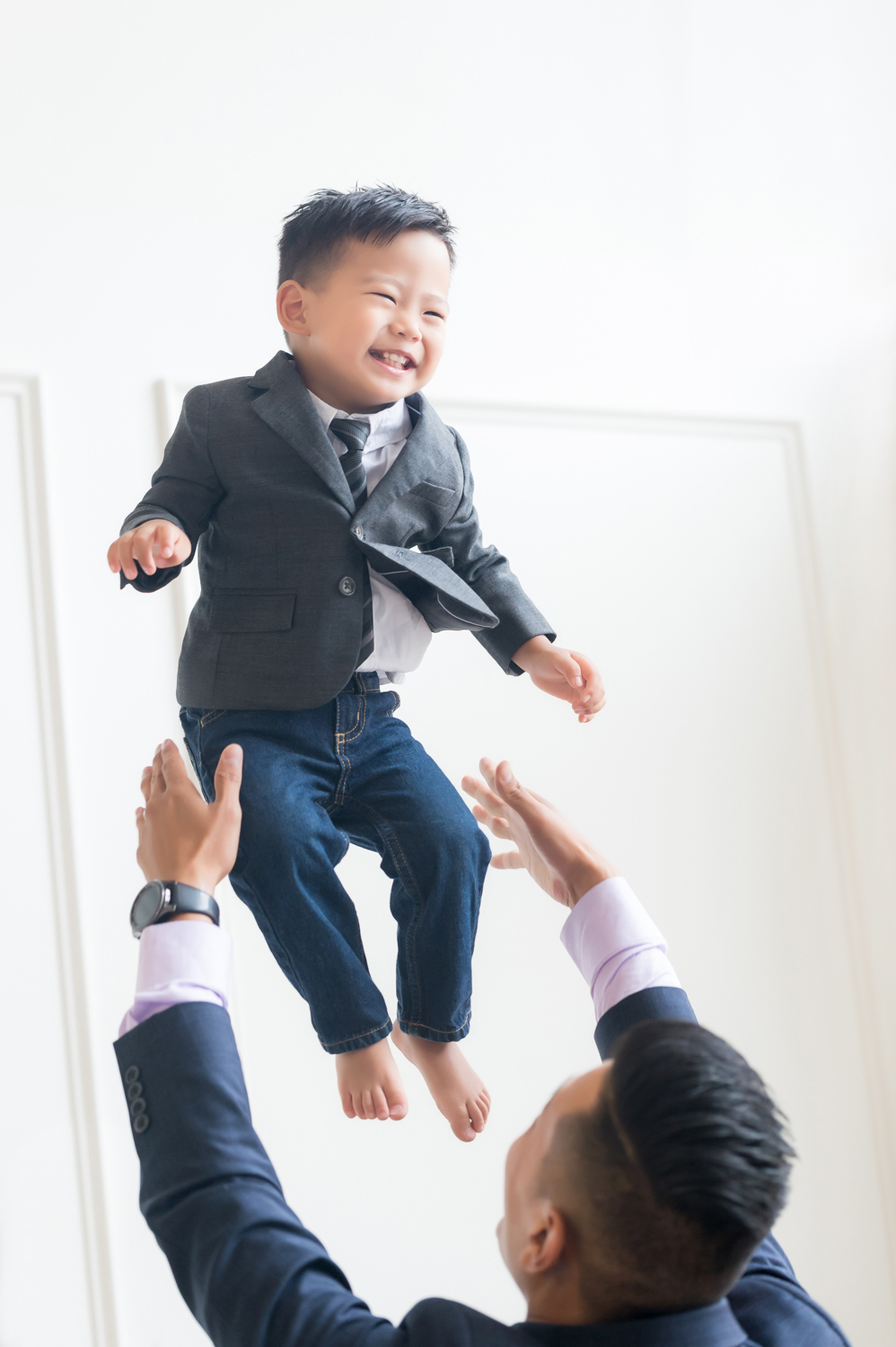 Father throws son in the air during a family photoshoot.