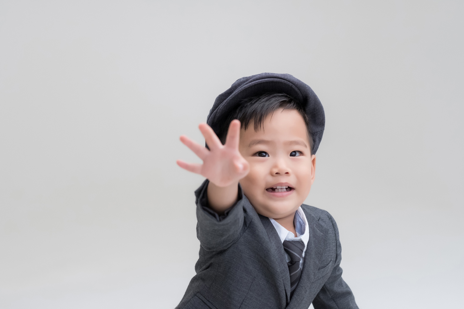 Little boy in suit reaches for camera.