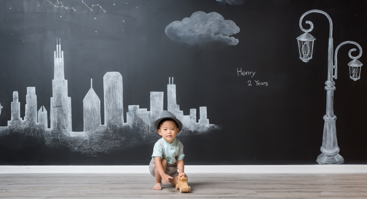 2-year-old boy sits in front of a chalkboard with the Chicago Skyline during a photo session.