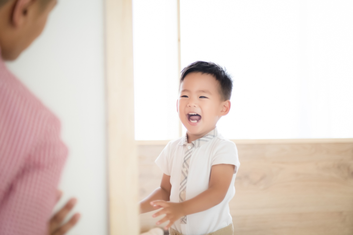 Toddler boy smiles and plays during a Chicago Baby photo session.