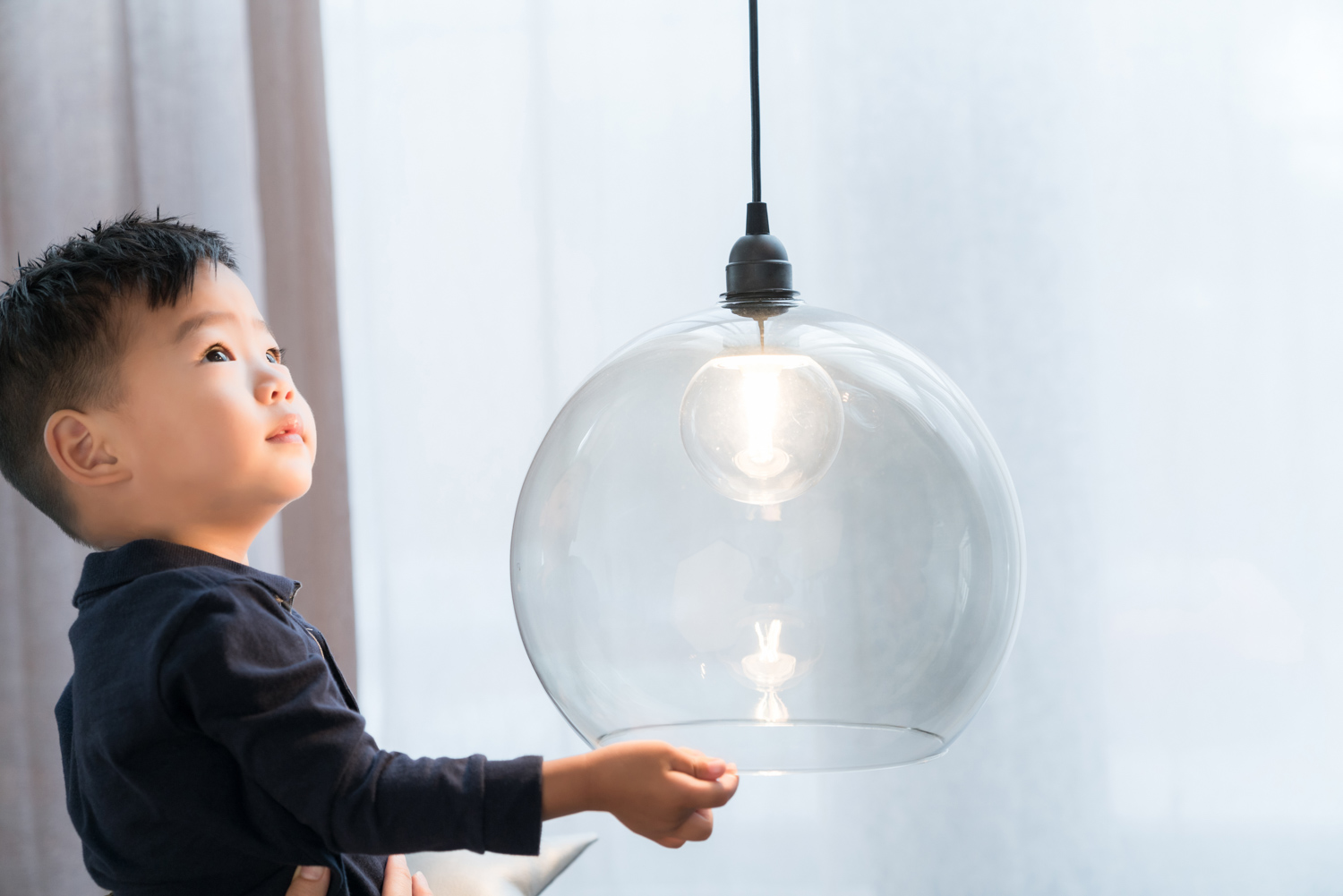 Korean toddler plays with decorative glass light.