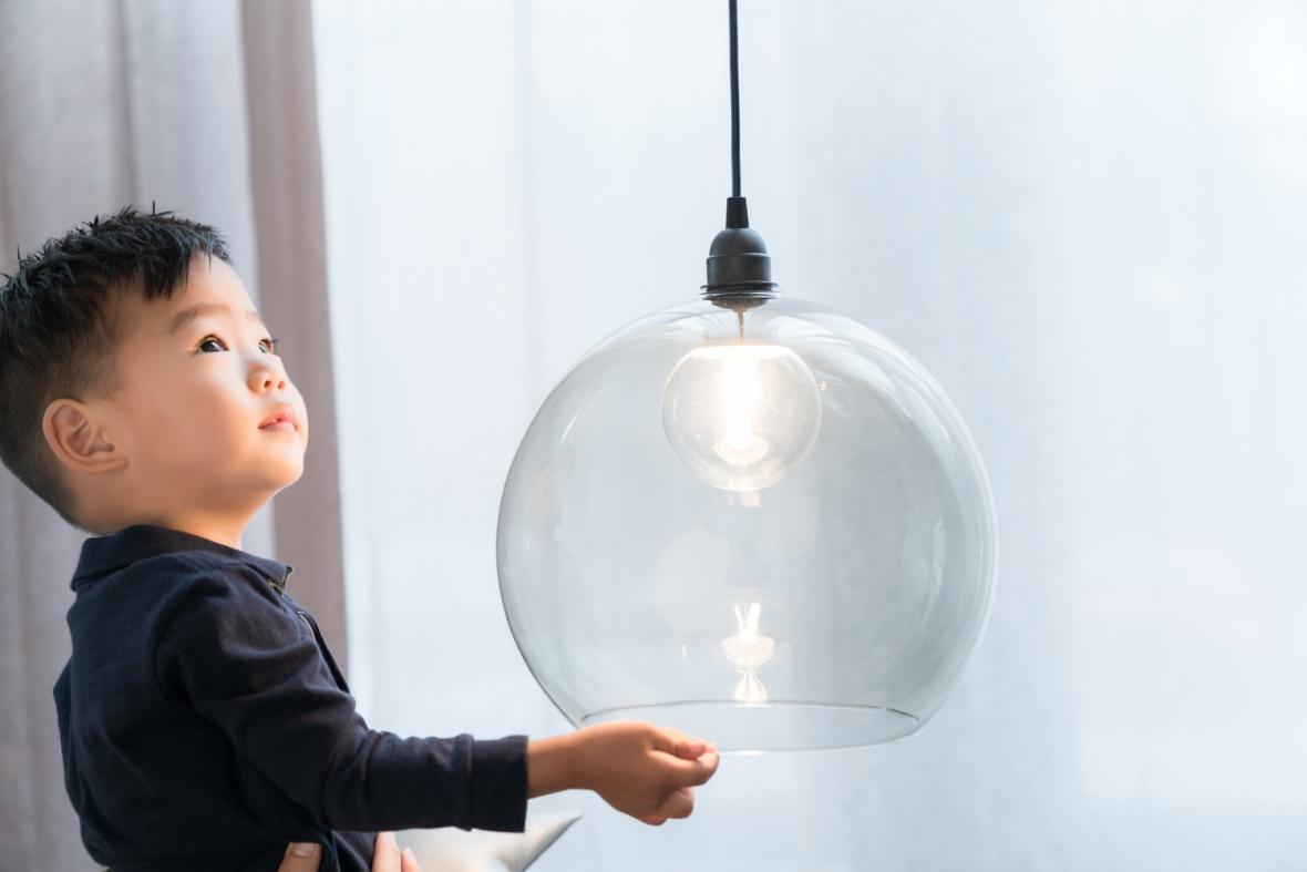 Korean toddler plays with decorative glass light.