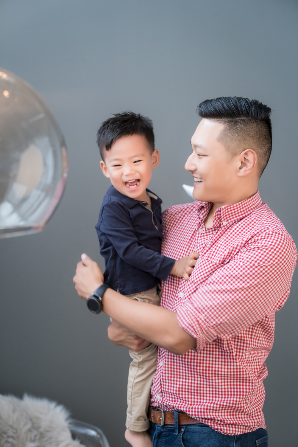 Father holds son and smiles.