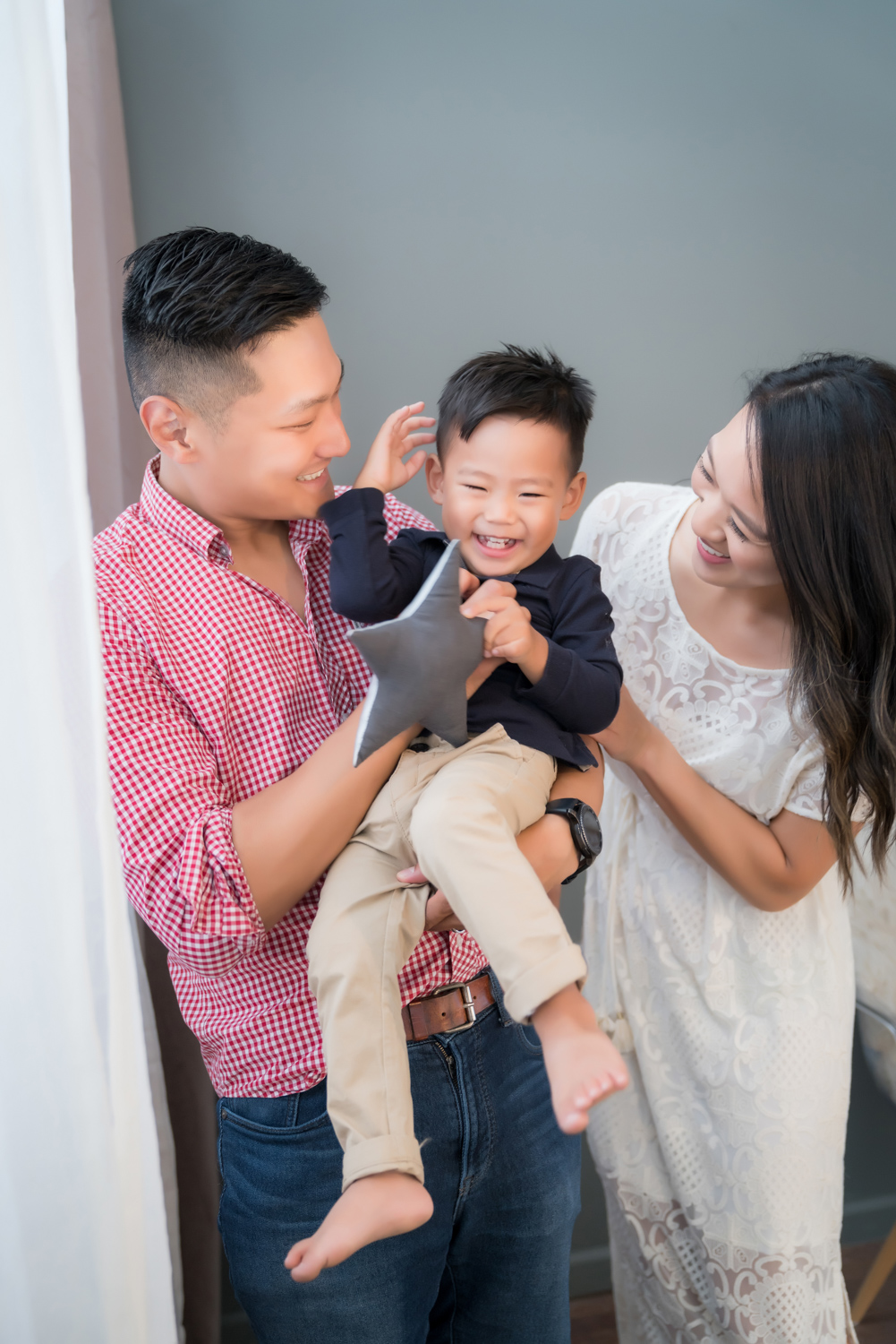 Parents tickle son and smile during family photoshoot in Chicago photo studio.