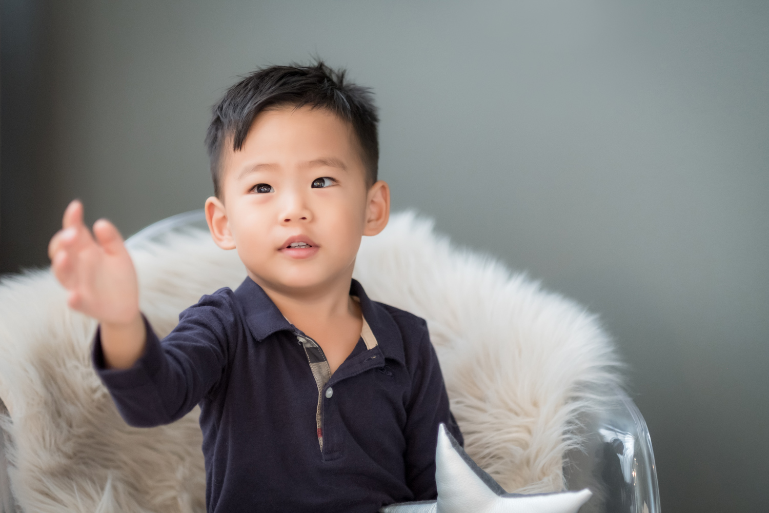 Little boy sits on a faux fur blanket and looks off camera during a photoshoot.