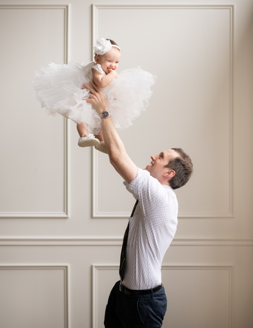 Dad tosses baby in the air during a Chicago family photoshoot.