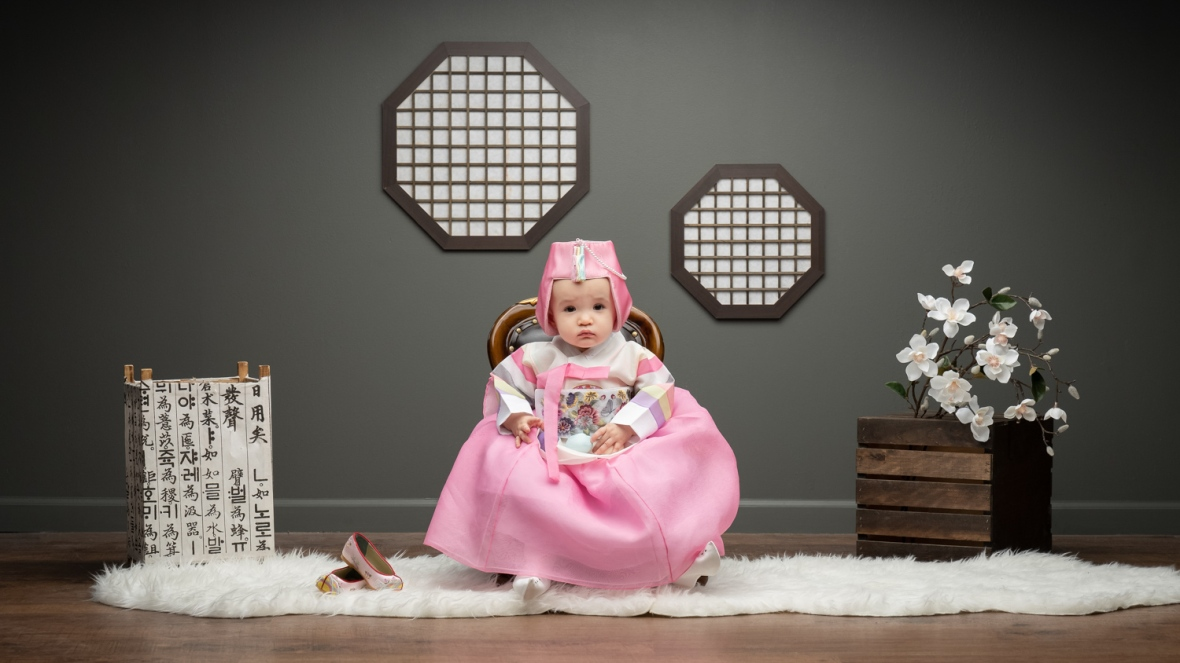 One-year-old baby wears a traditional Korean costume for first birthday photos.