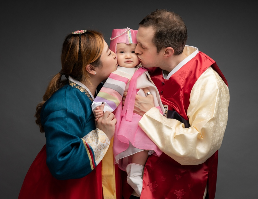 Parents kiss baby in traditional Korean outfits.