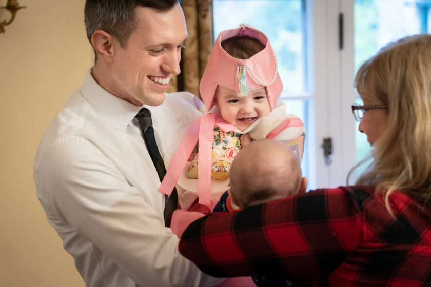 Dad holds daughter as they greet party guests for her first birthday.