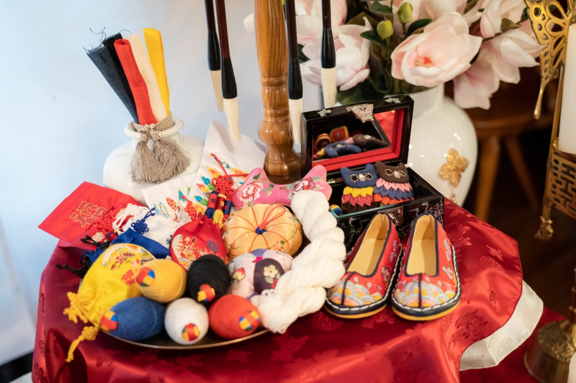 Traditional Korean shoes and toys are laid on a second table at Layla's first birthday party.