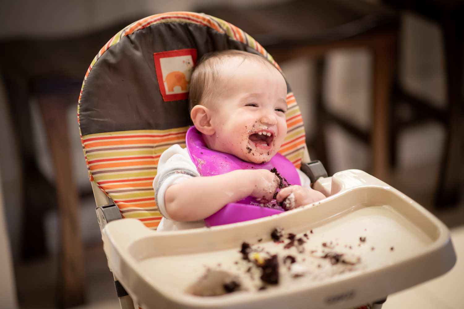 Layla laughs in her highchair, covered in cake.