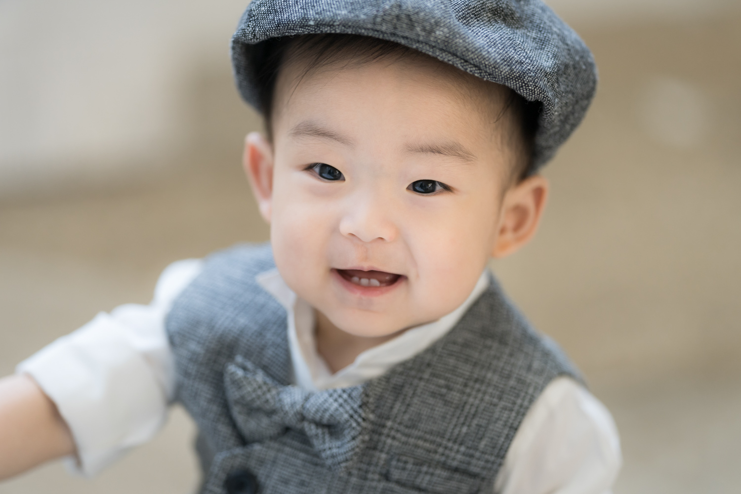 Baby in bow tie and cap smiles during Chicago baby photoshoot.