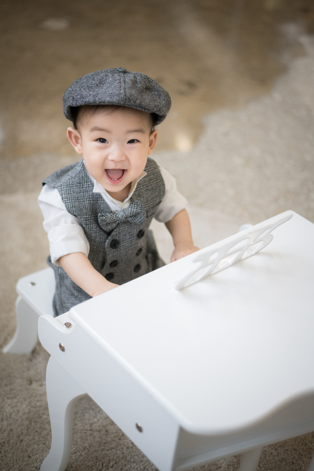 Toddler boy smiles and plays miniature piano in a suit.