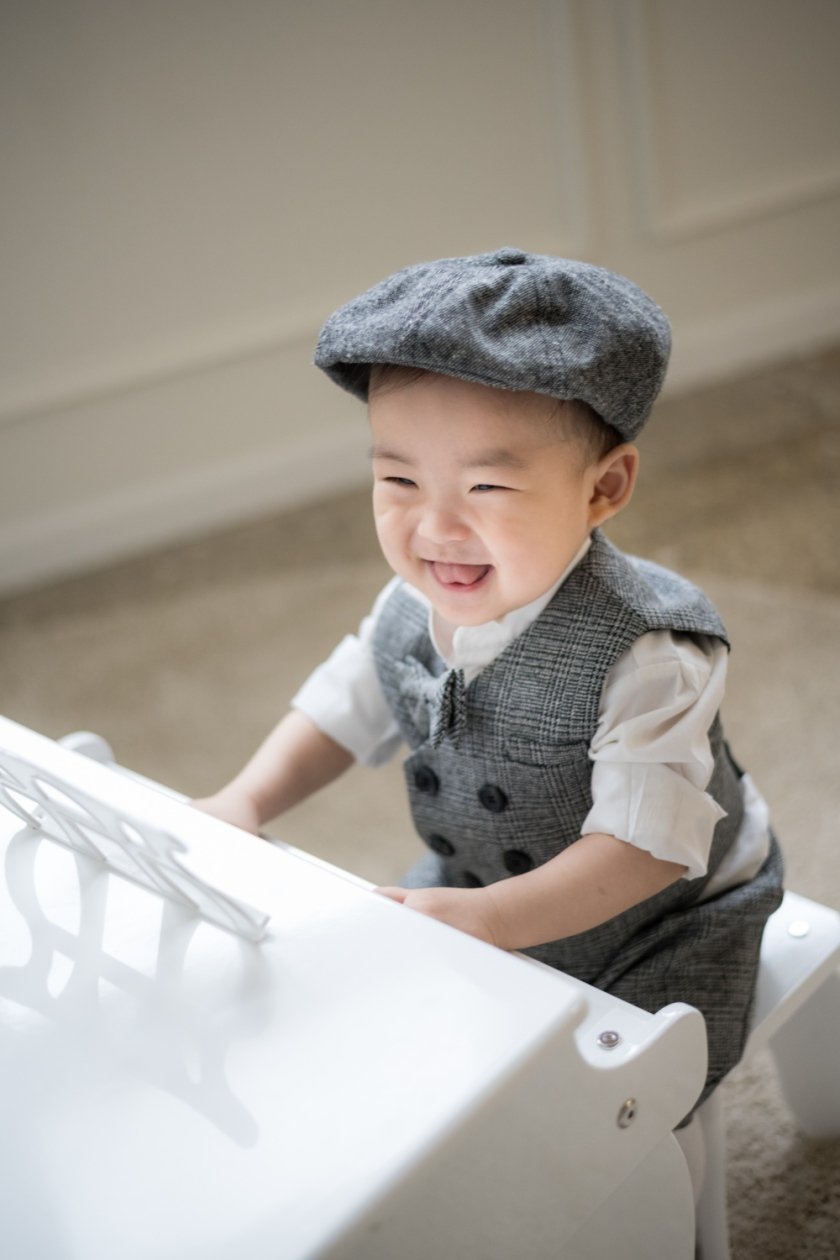 Baby boy plays mini piano in a grey suit during Chicago family photoshoot.
