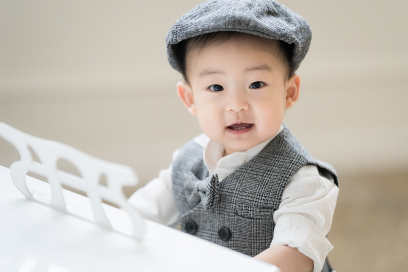 Baby looks at camera during family photoshoot while playing piano.