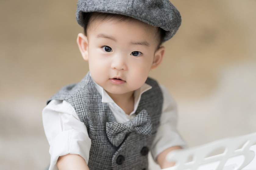 Baby wears a grey suit and bow tie during baby photo session.